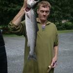 jeden z panów z kempingu Utladalen ze świeżo złowionym łososiem