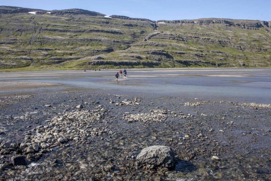 Islandia grupa przechodzaca przez fjord podczas odpływu